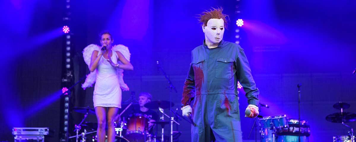 Titelbild Partyband Das Fiasko. Sänger als Michael Meyers verkleidet, im Hintergrund Sängerin als Engel im blauem Bühnenlicht.