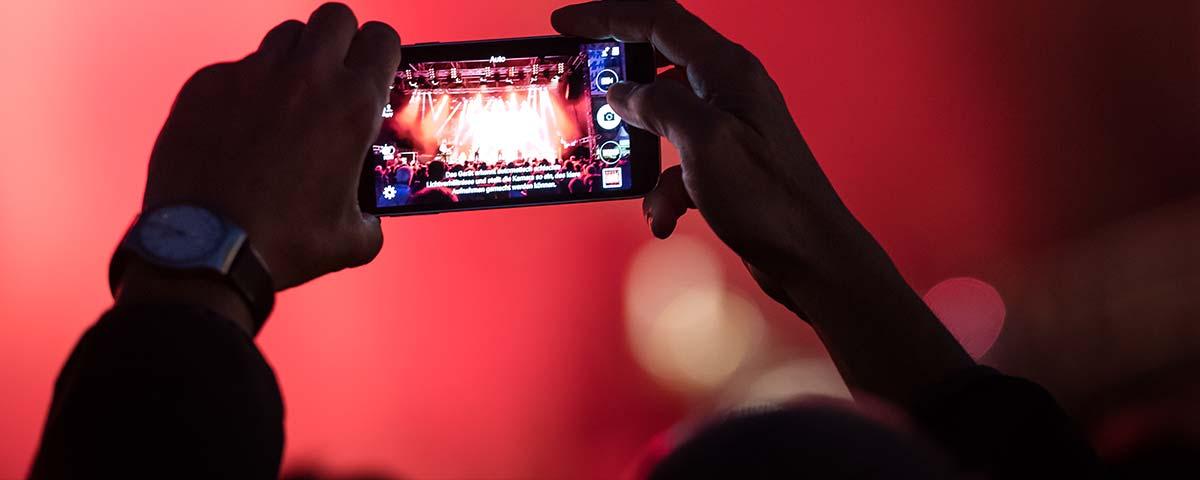 Titelbild Datenschutz. Fan hält Handy hoch und filmt.