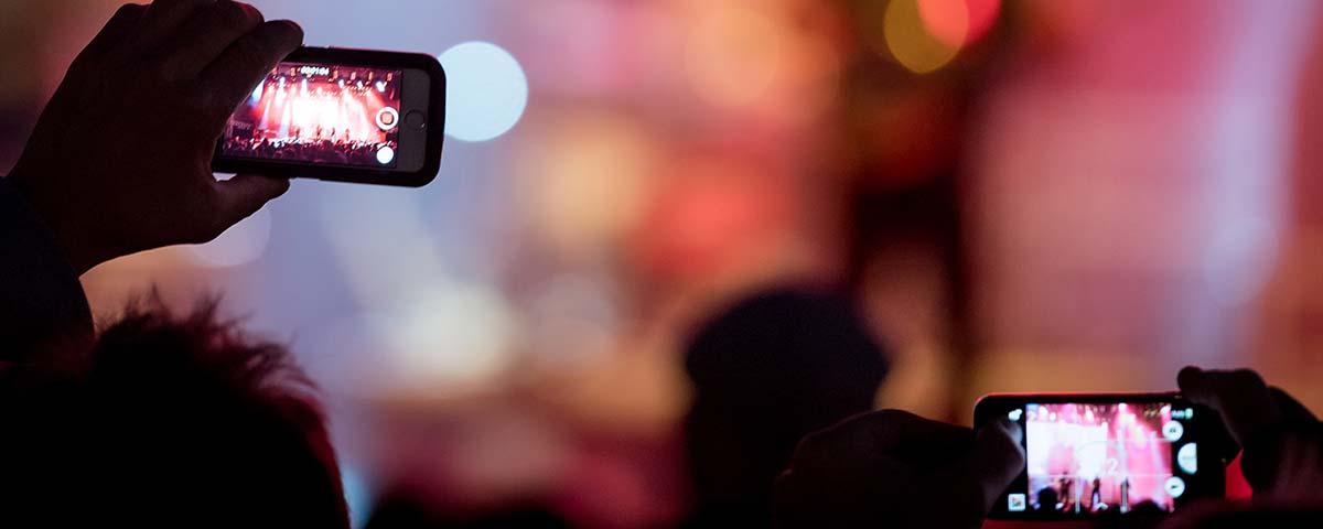 Titelbild Impressum. Publikum hält Handy Richtung Bühne