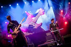 Gitarrist von Zack Zillis im Vordergrund. Im Hintergrund Gitarre auf großer leinwand