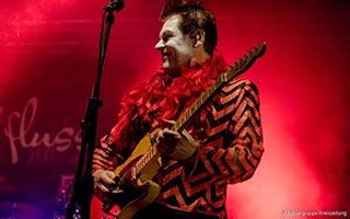 Gitarrist der Coverband im rotem Scheinwerferlicht auf einer Firmenfeier