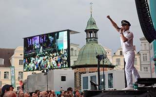 Sänger von der Seite. Im Hintergrund große Videoleinwand bei der NDR Sommertour Stadtfest