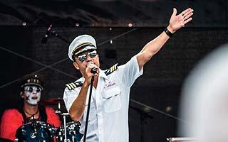 Sänger der Partyband in Kapitänsverkleidung mit Schlagzeuger im Hintergrund