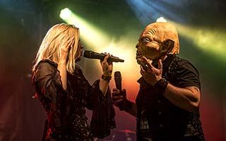 Sänger mit Maske und und Sängerin im Bühnenlicht