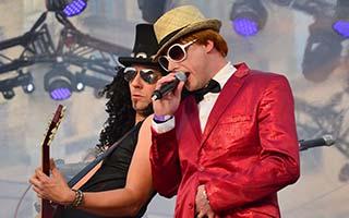 Sänger als Elton John verkleidet mit Gitarrist Slash auf einem Zeltfest