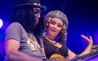 Gitarrist als Slash verkleidet zusammen mit Sängerin auf einem Zeltfest