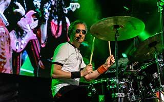 Schlagzeuger der Partyband Zack Zillis von der Seite mit Leinwand im Hintergrund