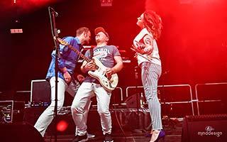 Gitarrist in der Mitte von Sänger und Sängerin während einem Gitarrensolo