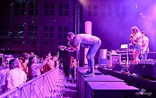 Blick von der Seite auf die Bühne. Sänger agiert mit Publikum