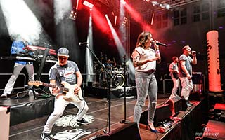 Die Partyband BiBa auf einer Stadtfestbühne im rotem Bühnenlicht