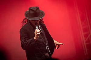 Sänger verkleidet als Udo Lindenberg im rotem Bühnenlicht