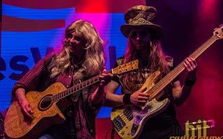 Gitarristin und Bassist im rotem Bühnenlicht