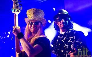 Bassist und Sänger im blauem Bühnenlicht. Beide schauen in die Kamera
