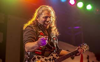 Gitarrist zeigt mit Finger in die Kamera und grinst
