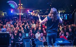 Foto von der Bühne aus zeigt Sänger von hinten Richtung Publikum