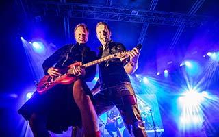 Gitarrist und Sänger im blauem Bühnenlicht auf einem Stadtfest