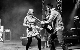 Gitarrist mit Sängerin beim abrocken auf einer Stadtfestbühne