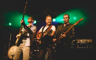 Sänger steht in der Mitte vom Bassist und Gitarrist im grünem Bühnenlicht